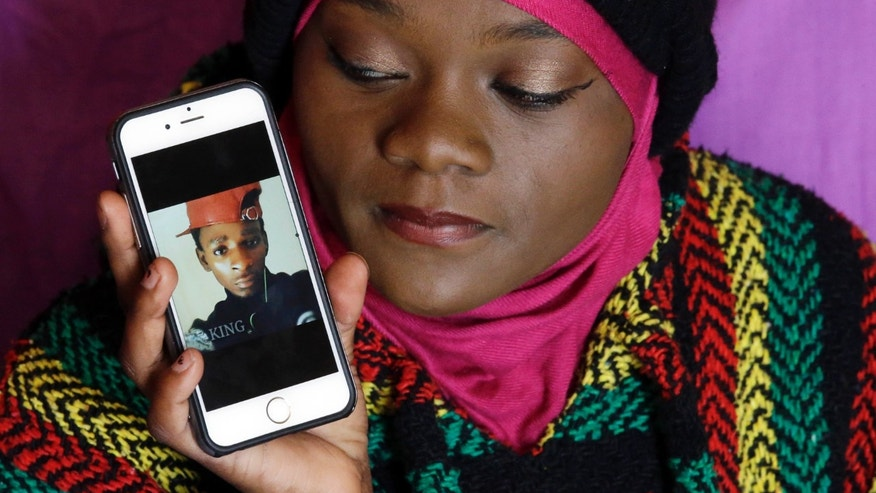 Abdi Mohamed's cousin Muslima Weledi holds a photograph of him during a interview Thursday, March 3, 2016, Salt Lake City.