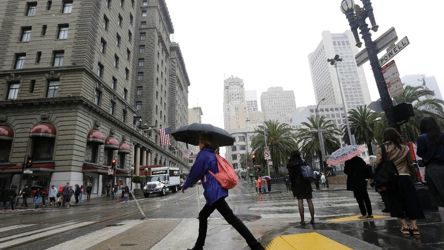 A woman carries an umbrella as she crosses Powell Street in San Francisco.