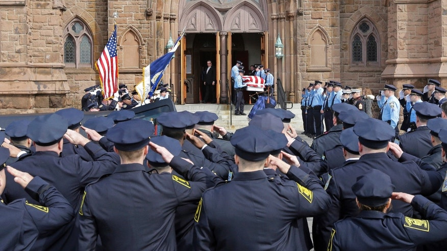 Police salute the casket of Officer Ashley Guindon as pallbearers exit Sacred Heart Church.