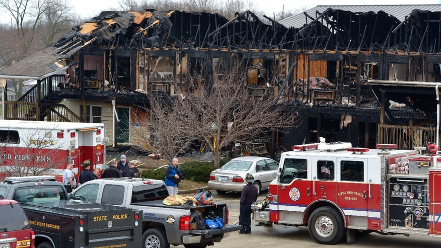 Units of the Winchester Fire Department remain on the scene as investigators with the Kentucky State Police Arson Investigation Division inspect the remains of a unit of the B&P Apartments, Friday, March 11, 2016 in Winchester Ky.