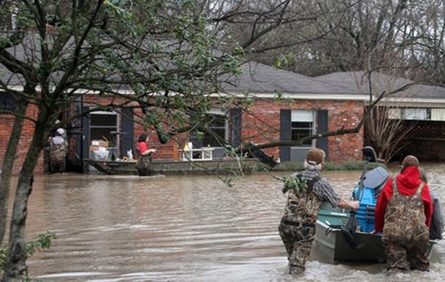 Volunteers return to a flooded house in Clarksdale, Miss., Friday, March 11, 2016, to assist the owners retrieve personal items as flood waters continued to rise following another morning of rain. (Troy Catchings/The Clarksdale Press Register, via AP)  /The Press Register via AP) MANDATORY CREDIT
