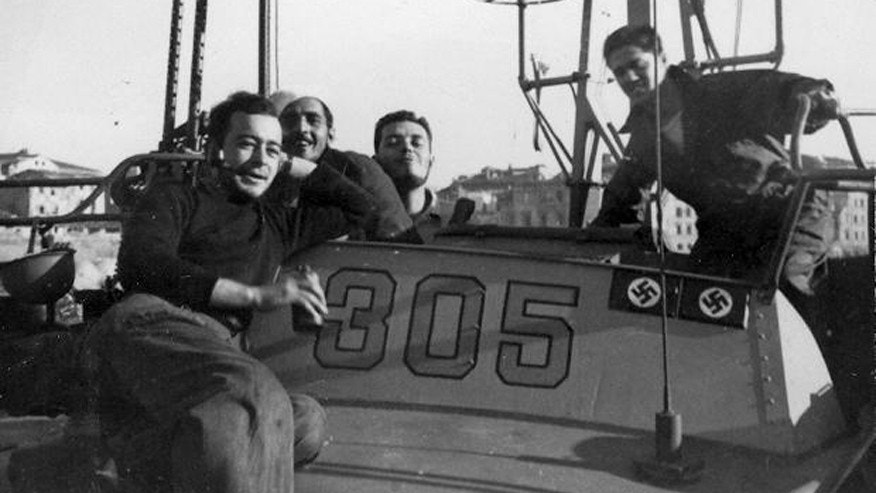 Joseph Brannan, Lawrence Petroni, Gregory Dosch, and George Rowland relax on the bridge and chart house of PT-305. Two swasktikas represent a German Flak lighter that PT-305 sank during the Invasion of Elba in 1944, and an Italian MAS boat she sank near Leghorn, Italy in 1945.