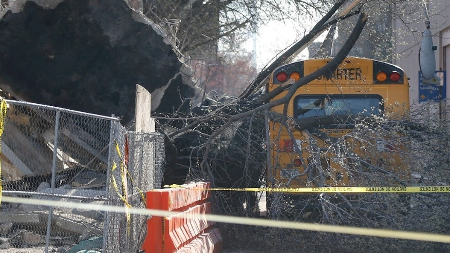 Debris from a building under demolition rests on a school bus.