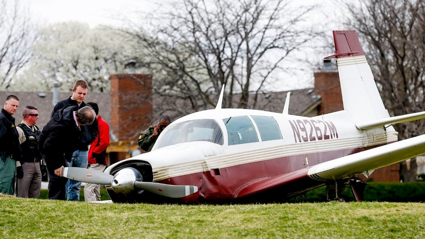 n this Friday, March 18, 2016 photo, authorities check out a small plane that crashed on the 14th hole at the Tallgrass Country Club in Wichita, Ks.