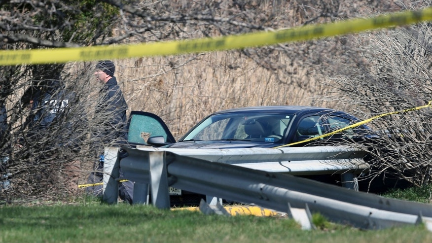 Investigators walk near a car with a shattered window at the scene where an off-duty cop was shot dead in New Jersey.