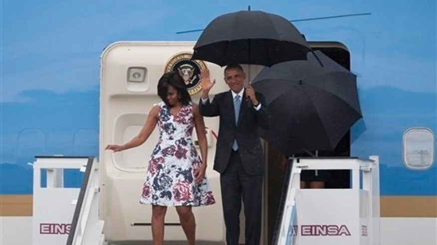 President Barack Obama waves from Air Force One as he arrives accompanied by first lady Michelle Obama at Jose Marti International Airport in Havana, Cuba, Sunday, March 20, 2016. Obama became the first U.S. president to visit the island in nearly 90 years. (AP Photo/Fernando Medina)