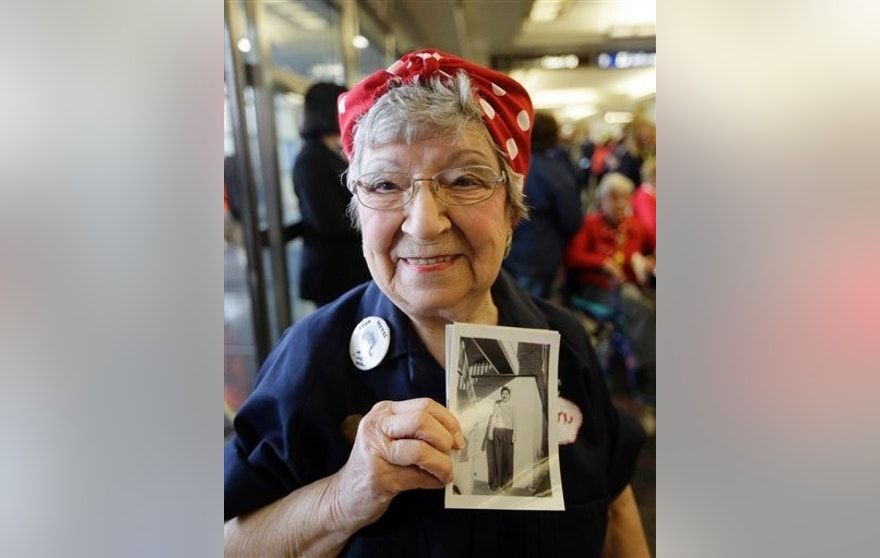 "Former Rosie, T. Ogden of Aurora, Ill. shows a photo of herself after greeting fellow Rosies from Michigan on their arrival at the Ronald Reagan Washington National Airport, Tuesday, March 22, 2016 in Washington. Seven decades after their ""we can do it"" attitude proved invaluable to the Allied victory in World War II, some ""Rosie the Riveters"" are being honored with a flight to Washington, D.C. The women will check out the National World War II Memorial and Arlington National Cemetery, and have lunch with members of Congress. (AP Photo/Carlos Osorio)"