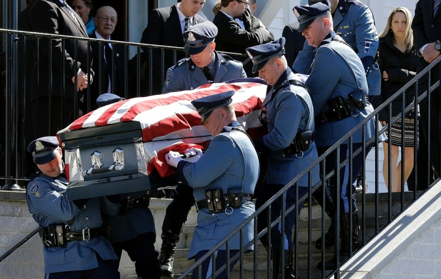Pallbearers carry the casket of Mass. State Trooper Thomas L. Clardy out of Saint Michael Church as his widow, Reisa, far right, follows after his funeral, Tuesday, March 22, 2016, in Hudson, Mass. Clardy, was killed when a car slammed into his cruiser as he was stopping another driver. (AP Photo/Elise Amendola)