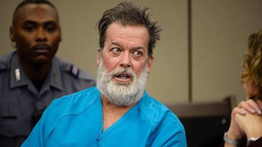 FILE - In this Dec. 9, 2015 file photo, Robert Lewis Dear, middle, talks during a court appearance in Colorado Springs, Colo. A defense attorney for Dear, who acknowledges killing three people at a Colorado Planned Parenthood clinic, asked a judge to commit his client to a psychiatric hospital for treatment but did not reveal whether a mental health exam found him competent to continue with his criminal case, on  Thursday, March 24, 2016.  (Andy Cross/The Denver Post via AP, Pool, File)