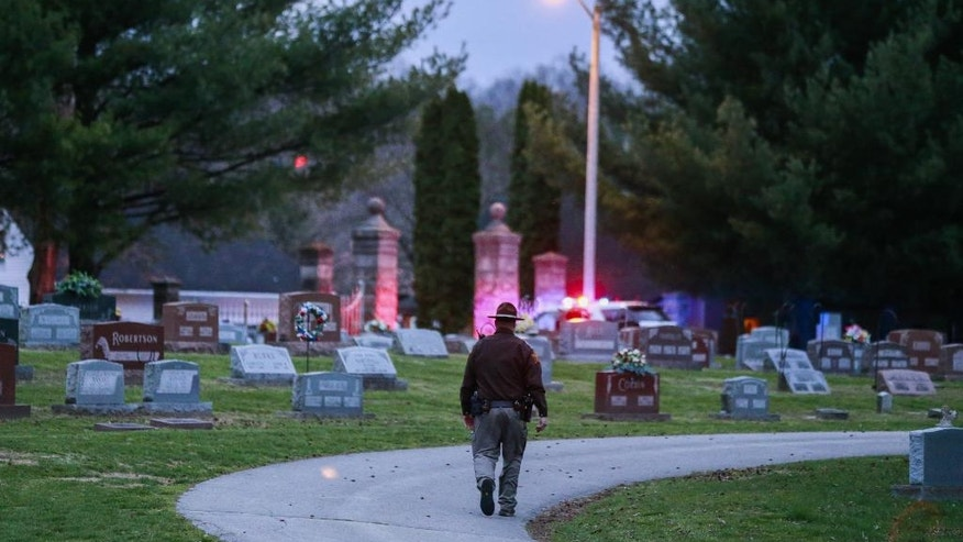 In a Wednesday, March 23, 2016 photo, a police officer looking for a missing toddler Shaylyn Ammerman walks through Riverside Cemetery in Spencer, Ind. Shaylyn Ammerman was reported missing from her crib by her grandmother Wednesday morning. The search continued Thursday. (Jeremy Hogan/(/The Herald-Times via AP) MANDATORY CREDIT