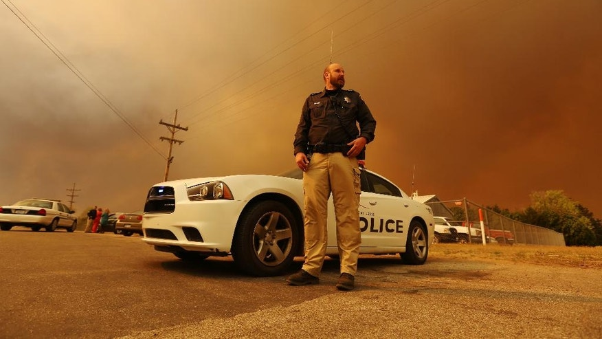 Medicine Lodge, Kan., police officer Todd Geist stands under a cloud of smoke and blowing dirt as he blocks traffic from traveling west on Stolp Avenue in Medicine Lodge, Kan., Wednesday, March 23, 2016. The road that turns into River Road to Lake City was closed due to smoke from a large range grass fire west of the city. (Travis Morisse/The Hutchinson News via AP) MANDATORY CREDIT