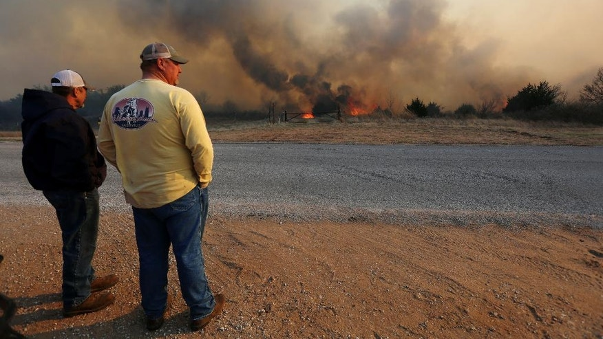 Jeff Clark and Roger Van Rankin watch the fire east of Lake City, Kan., Wednesday, March 23, 2016. The two were watching to see if the fire would jump the road onto Clark's ground. (Travis Morisse/The Hutchinson News via AP) MANDATORY CREDIT