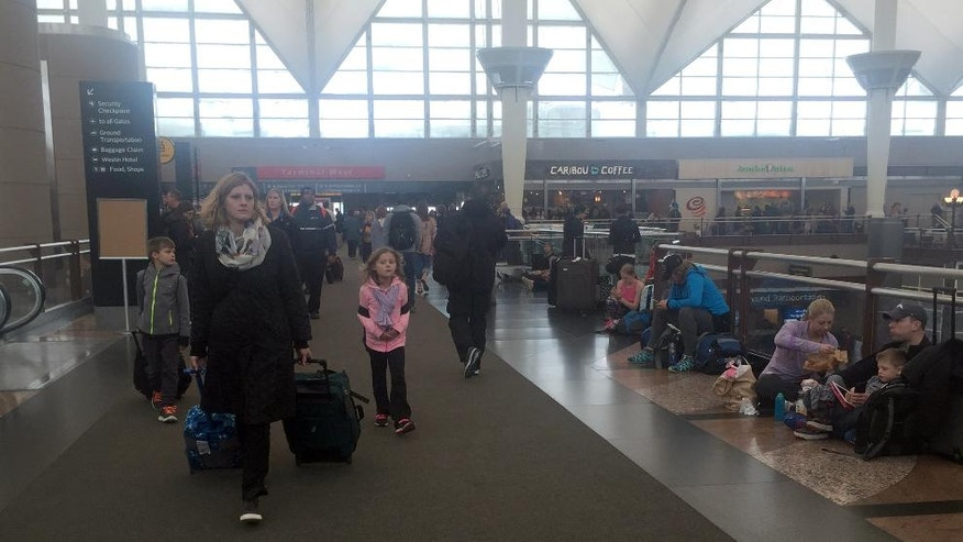 In this photo provided by Glynnis O'Connell, passengers move about in the main terminal of Denver International Airport on Wednesday, March 23, 2016, as a spring storm, packing high winds and wet, heavy snow, forced officials to shut down the airport. The storm has wreaked havoc for travelers in the intermountain West, closing roads and even schools as the storm rumbles through on to the plains. (Glynnis O'Connell via AP) MANDATORY CREDIT