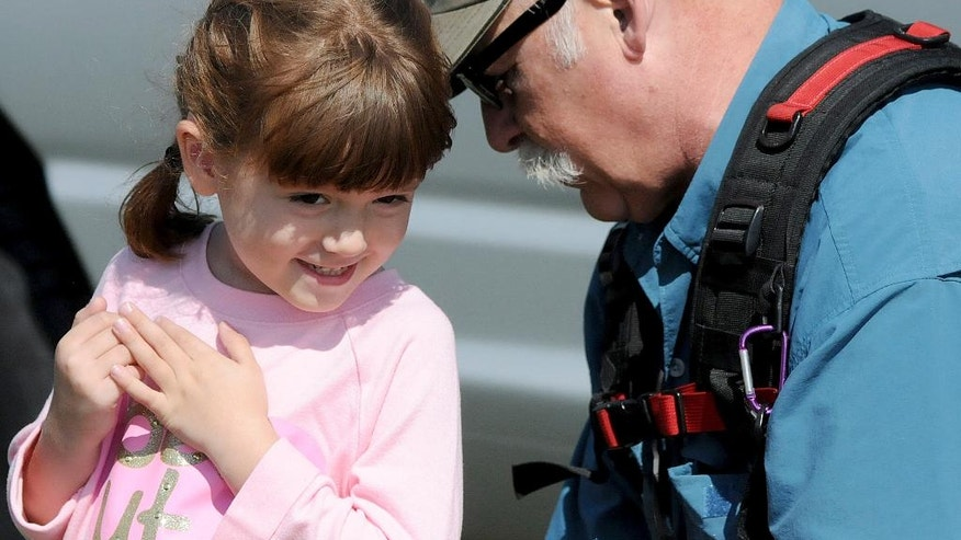 "This Friday, Sept. 19, 2015 photo shows Elizabeth ""Lizzy"" Myers, left, being fitted for a microphone by a CBS sound man before taping a segment in Lucas, Ohio. Myers, a 5-year-old Ohio girl whose parents created a ""visual bucket list"" for her because she's slowly going blind is going to meet Pope Francis. Steve Myers told the Mansfield News Journal on Thursday, March 24, 2016, that his daughter Elizabeth ""Lizzy"" Myers is visiting the Vatican next week. (Jason J. Molyet/News Journal via AP) NO SALES; MANDATORY CREDIT"