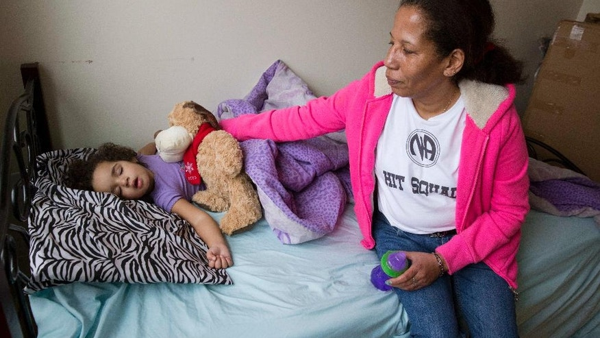 "In this photo taken March 24, 2016, Sharon Johnson reaches out to her napping granddaughter Aries, 2, in her apartment in Lynn, Mass. Johnson calls herself an addict, although she's been sober for three years now. She started by smoking pot and eventually moved to crack cocaine. Her daughter has tried heroin and ""I believe I'm going to pull her out of the gutter someday,"" she laments.  (AP Photo/Michael Dwyer)"