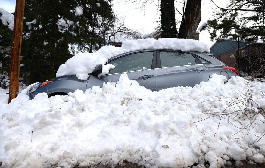 A car sits buried in snow from the blizzard on 9th Street in Boulder, Colo., on Thursday, March 24, 2016. (Jeremy Papasso/Daily Camera via AP)
