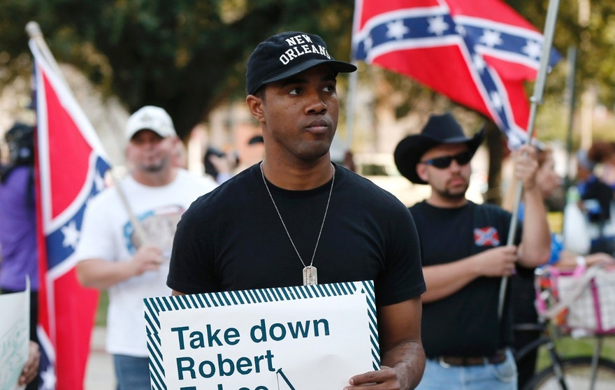 FILE - In this Dec. 10, 2015 file photo, an unidentified participant holds a sign during a rally lead by the Take 'em Down Coalition, as confederate heritage supporters bear confederate flags nearby in front of City Hall in New Orleans.  Backlash has stalled work to remove four Confederate monuments in New Orleans. The backlash has come in the form of lawsuits, boycotts, a possible torching of a contractor's car, alleged death threats against contractors and protests. Now, a bill in the Louisiana Legislature is taking aim at the removal. (AP Photo/Gerald Herbert, File)