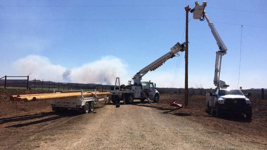 New utility poles are installed in rural rural Barber County near Medicine Lodge, Kan., on Thursday, March, 25, 2016. A fire that started Tuesday in Oklahoma has now burnt near 400, 000 acres in Kansas and Oklahoma. (Amy Bickel/The Hutchinson News via AP)