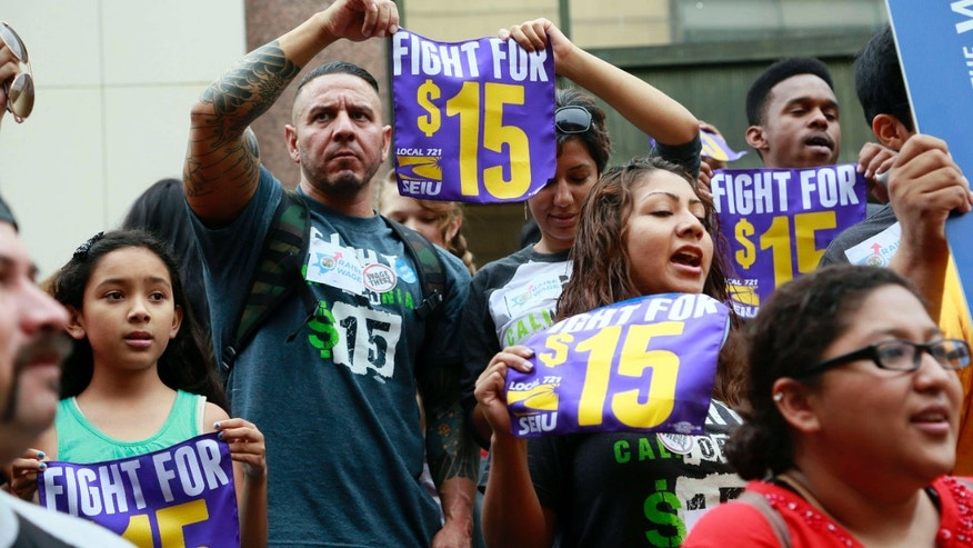FILE - In this Tuesday, July 21, 2015 file photo, workers hold a rally in Los Angeles in support of the Los Angeles County Board of Supervisors' proposed minimum wage ordinance.