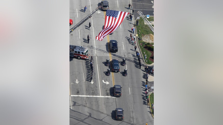 The funeral procession for Howard County Deputy Carl Koontz proceeds under a garrison flag as it makes it way from Northwestern High School to the cemetery in Kokomo, Ind., Tuesday, March 29, 2016. Koontz was killed in the line of duty while serving a warrant on March 20 in Russiaville. (AP Photo/Michael Conroy)