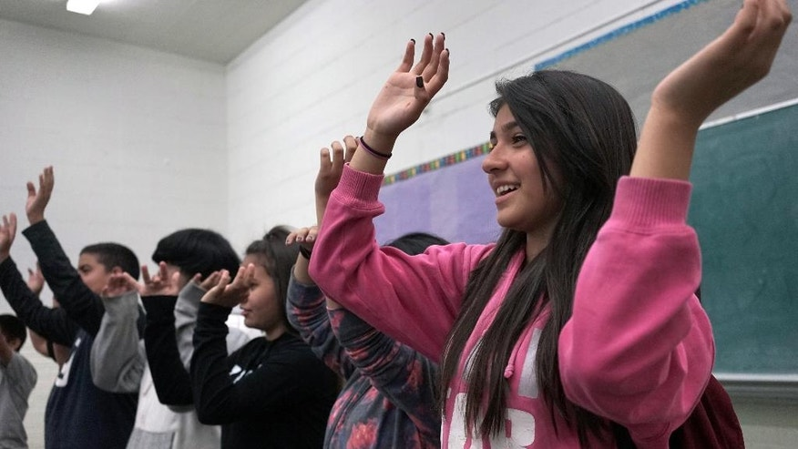 "In this Tuesday, March 8, 2016 photo, student Maleenah Vera waves her arms during a music class at Stevenson Middle School in East Los Angeles. Los Angeles Unified School District, the nation's second largest, once had a $76.8 million budget for arts education, but years of cuts and layoffs wiped all arts classes from dozens of schools - leaving many students in the entertainment capital of the world with no music, visual arts, dance or theater instruction. That is slowly starting to change: The district is trying to enlist Hollywood studios to ""adopt"" LA Unified schools and provide them with equipment, mentorships and training. (AP Photo/Christine Armario)"
