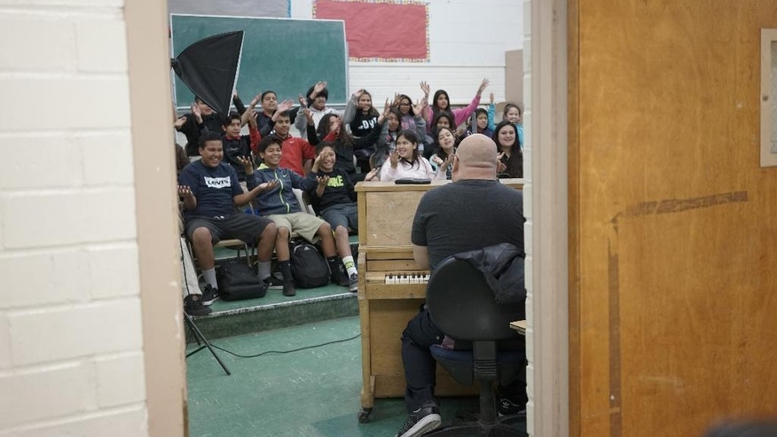 "In this Tuesday, March 8, 2016 photo, teacher Steve Shin sings with students during a music class at Stevenson Middle School in East Los Angeles. Los Angeles Unified School District, the nation's second largest, once had a $76.8 million budget for arts education, but years of cuts and layoffs wiped all arts classes from dozens of schools - leaving many students in the entertainment capital of the world with no music, visual arts, dance or theater instruction. That is slowly starting to change: The district is trying to enlist Hollywood studios to ""adopt"" LA Unified schools and provide them with equipment, mentorships and training. (AP Photo/Christine Armario)"