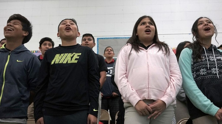 "This Tuesday, March 8, 2016 photo, students Landon Palacios, from left, Diego Castillo, Karen Nicifori and Jennifer Munoz sing during a music class at Stevenson Middle School in East Los Angeles. Los Angeles Unified School District, the nation's second largest, once had a $76.8 million budget for arts education, but years of cuts and layoffs wiped all arts classes from dozens of schools - leaving many students in the entertainment capital of the world with no music, visual arts, dance or theater instruction. That is slowly starting to change: The district is trying to enlist Hollywood studios to ""adopt"" LA Unified schools and provide them with equipment, mentorships and training. (AP Photo/Christine Armario)"