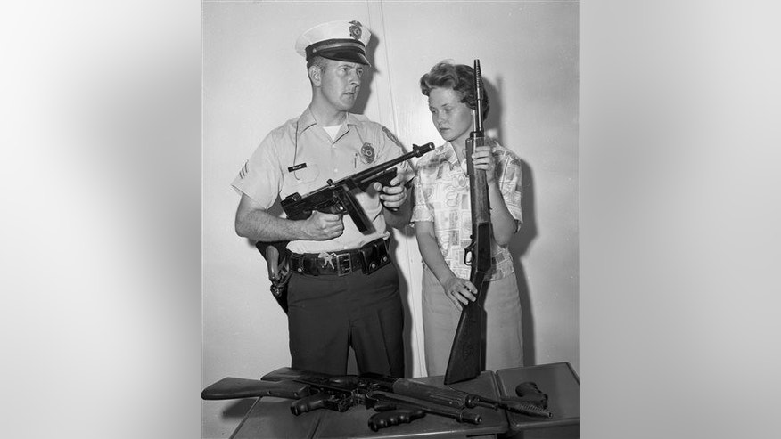 In this 1961 photo, Tucson Police Sgt. Tom Keeley holds a Colt Thompson submachine gun and secretary Linda Bradfield holds a Winchester Model 1907, with other guns confiscated from the John Dillinger gang during Dillinger's capture in Tucson, Ariz., in 1934