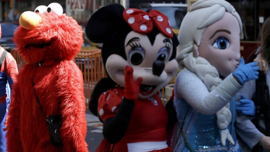 Costumed characters work for tips in Times Square.