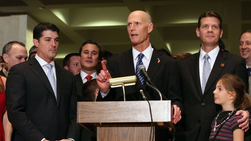 Gov. Rick Scott addresses the crowd flanked by House Speaker Steve Crisafulli, R-Merritt Island, left, and Senate President Andy Gardiner, R-Orlando, at the end of session, Friday, March 11, 2016, in Tallahassee, Fla.