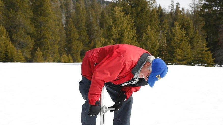 FILE- In this March 1, 2016 file photo, Frank Gehrke, chief of the California Cooperative Snow Surveys Program for the Department of Water Resources, checks the depth of the snowpack at Phillips Station near Echo Summit, Calif. State surveyors will trudge through several feet of snow Wednesday, March 30, 2016, to manually measure what could be close to a normal Sierra Nevada snowpack for this time of year. (AP Photo/Rich Pedroncelli, File)
