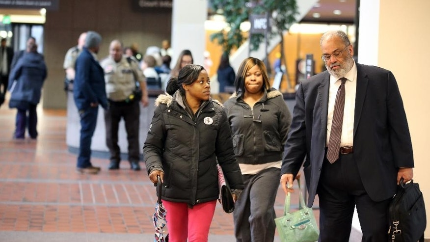 Jamar Clark's sisters Tiffany Roberson and Sharice Burns arrive at the at the Hennepin County Government Center with their attorney Albert Goins,  Wednesday, March 30, 2016, in Minneapolis. Hennepin County Attorney Mike Freeman on Wednesday announced his decision not to charge Officers Mark Ringgenberg and Dustin Schwarze in the shooting of 24-year-old Jamar Clark.  (Jerry Holt/The Star Tribune via AP)  MANDATORY CREDIT; ST. PAUL PIONEER PRESS OUT; MAGS OUT; TWIN CITIES LOCAL TELEVISION OUT