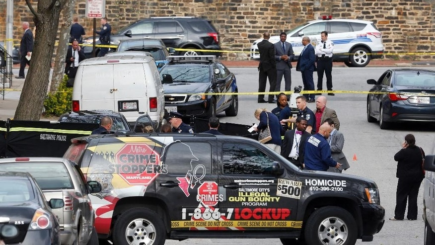 Officials investigate the scene of a police-involved shooting in Baltimore, Thursday, March 31, 2016. Baltimore police say two armed men are dead after plainclothes officers opened fire on them when they found the men aiming guns at someone across a street. (AP Photo/Patrick Semansky)