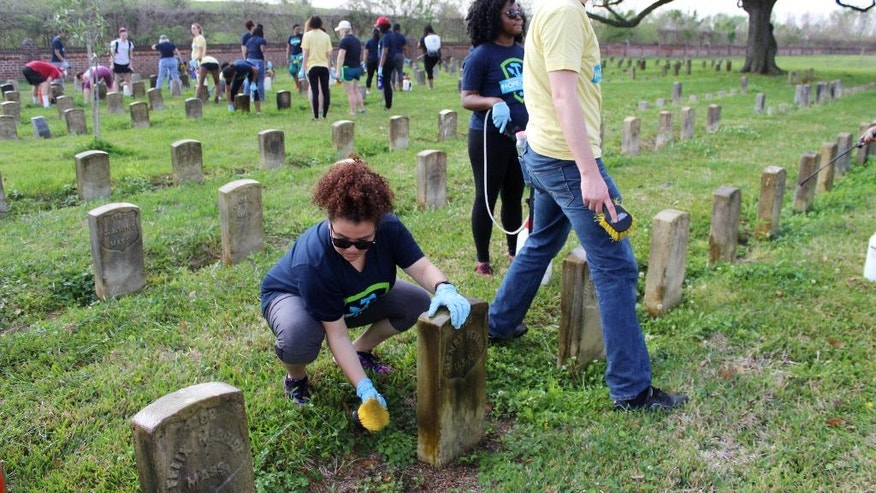 In this March 16, 2016 photo, volunteers perform maintenance on gravestones at Chalmette National Cemetery in Chalmette, La. College students on spring break joined hundreds of other volunteers at a cemetery dating to the Civil War, realigning hundreds of tilted headstones and scrubbing grime from thousands more. (AP Photo/Janet McConnaughey)