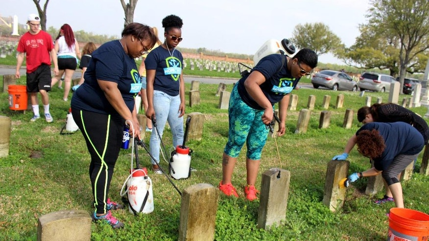 In a Wednesday, March 16, 2016 photo, Ohio State University students Willie Love, left,, of Cincinnati, and Ashauna Mathews, of Canton, Ohio, spray a cleaning solution on gravestones at Chalmette National Cemetery in Chalmette, La. Between them is Jasmine Harris, of Cleveland. They were among about 50 Ohio State students working at the cemetery, as part of a nearly month-long project organized by the National Trust for Historic Preservation. (AP Photo/Janet McConnaughey)