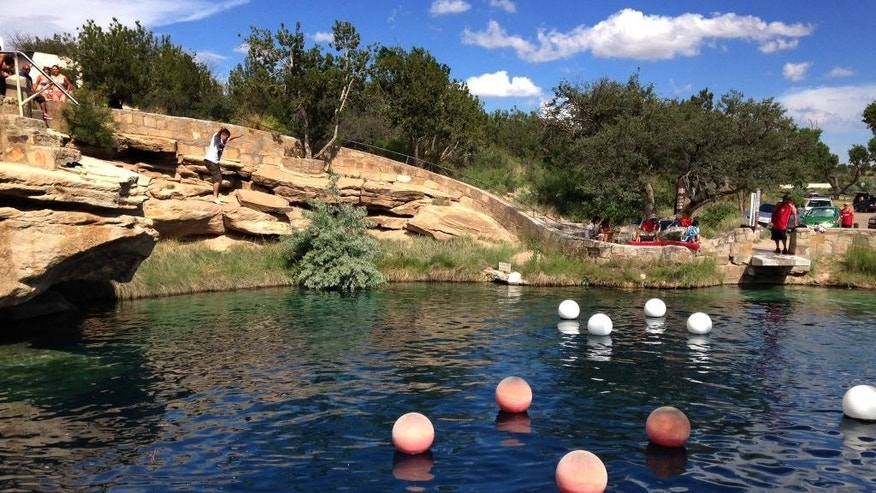 FILE - This June 6, 2015 file photo shows a boy leaping into the water at Blue Hole State Park in Santa Rosa, N.M. An eastern New Mexico police chief says an experienced California diver has died in an underwater cave beneath a swimming hole. Santa Rosa Police Chief Jude Gallegos says the initial investigation suggests 43-year-old Shane Thompson's death Saturday below the Blue Hole was an accidental drowning.(AP Photo/Susan Montoya Bryan, File)
