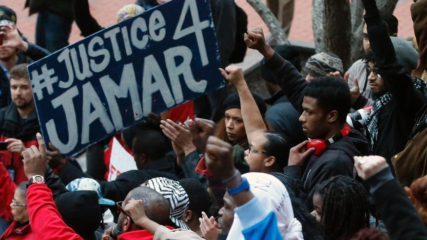 Demonstrators raise their fists in the air at the Government Center in Minneapolis on Wednesday, March 30, 2016, to protest County Attorney Mike Freeman's decision that no charges will be filed against two Minneapolis police officers in the fatal shooting of a black man, Jamar Clark, 24, in November 2015. (AP Photo/Jim Mone)