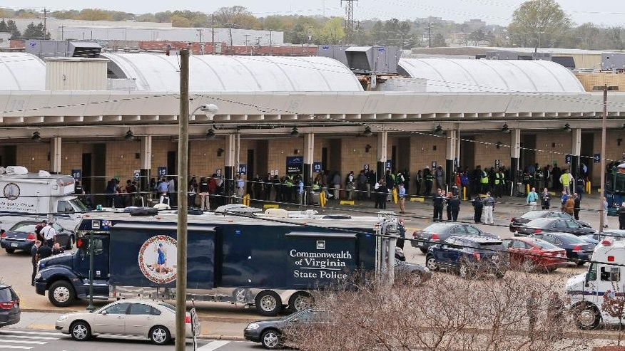 Police and rescue officials mingle with bus patrons outside the Greyhound Bus Station Thursday, March 31, 2016, in Richmond, Va. Virginia State Police say two troopers responding to a shooting at the Richmond bus station and a civilian have been taken to a hospital. A police spokeswoman says the shooting suspect was in custody. (AP Photo/Steve Helber)