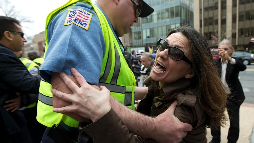Anti-Erdogan protestor Deniz Lohja, an American of Turkish descent, is prevented by a Washington police officer from crossing near the supporters of the Turkish President Recep Tayyip Erdogan, during a rally outside the Brookings Institution in Washington, Thursday, March 31, 2016, where Erdogan spoke.  (AP Photo/Manuel Balce Ceneta)