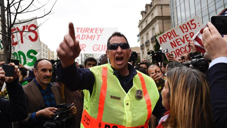 A police officer orders a pro-Erdogan woman to go to her corner in front of Brookings Institution in Washington, Thursday, March 31, 2016, where President Recep Tayyip Erdogan was speaking. (AP Photo/Sait Serkan Gurbuz)