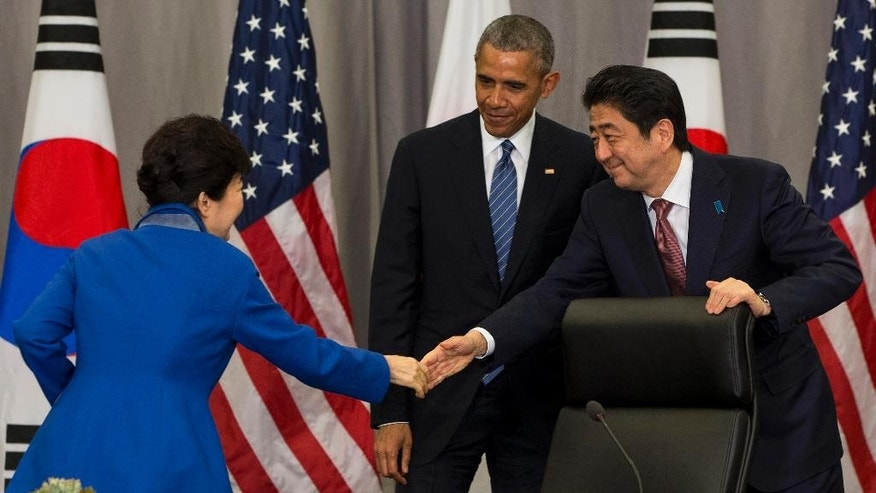 South Korean President Park Geun-hye, left, shakes hands with Japanese Prime Minister Shinzo Abe as President Barack Obama watches after their meeting at the Nuclear Security Summit in Washington, on Thursday, March 31, 2016. (AP Photo/Jacquelyn Martin)