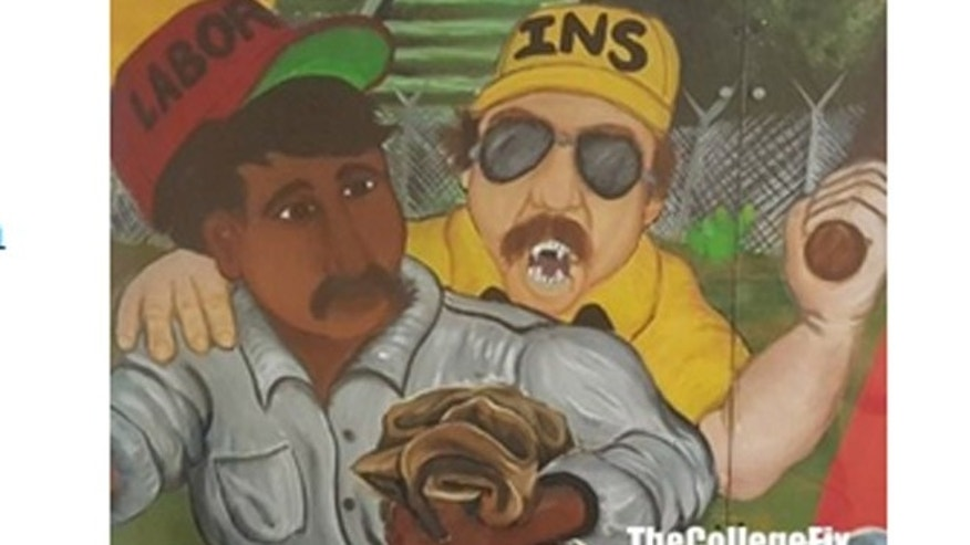 The mural shows a menacing border agent with fangs apparently poised to beat a laboroer. (The College Fix)
