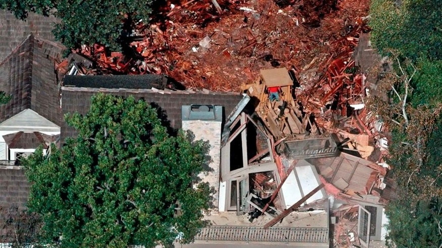FILE - In this July 29, 1998 file photo, crews demolish the former home of O.J. Simpson in the Brentwood area of Los Angeles. After nearly a month of testing, Los Angeles police detectives have concluded a knife found during the demolition was not the weapon used to kill Simpson's ex-wife Nicole Brown Simpson and her friend Ronald Goldman in 1994. Investigators ruled out the knife after weeks of forensic tests, Police Capt. Andy Neiman said Friday, April 1, 2016. (AP Photo/Mark J. Terrill, File)