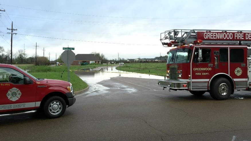 The Greenwood Fire Department blocks off Sgt. John A. Pittman Drive, Thursday, March 31, 2016, in Greenwood, Miss., to keep motorists from trying to navigate the flooded road from morning rains. (Tim Kalich/The Greenwood Commonwealth, via AP)