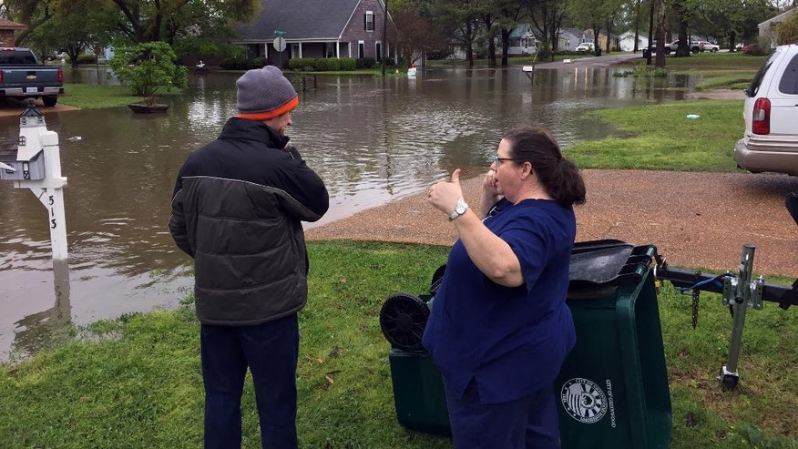 Lisa Ramsey, right, says in seven years at her West Jeff Davis Avenue home she's never seen the water so high as it got, Thursday, March 31, 2016, in Greenwood, Miss., as Justin Carpenter joins her in surveying the scene. The National Weather Service said Greenwood received 5 inches of rain between 1 a.m. and 5 a.m. Thursday. Greenwood and Leflore County schools and Pillow Academy were closed because of flooding-related problems on Thursday. (Tim Kalich/The Greenwood Commonwealth via AP)