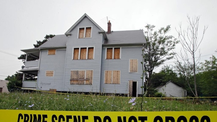 FILE - In this July 22, 2013, file photo crime scene tape surrounds a boarded up home in East Cleveland, Ohio. The trial for Michael Madison charged in the slayings of multiple women whose bodies were found wrapped in garbage bags is scheduled to begin Monday, April 4, 2016, in Cleveland with jury selection. (AP Photo/Mark Duncan, File)
