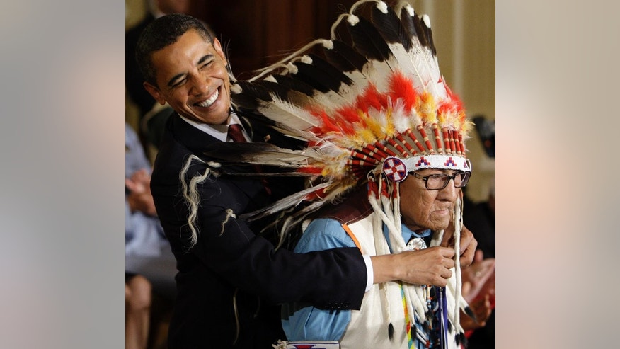 FILE - In this Aug. 12, 2009 file photo, President Barack Obama reaches around the head dress of Chief Joseph Medicine Crow to place a 2009 Presidential Medal of Freedom around his neck during a ceremony in the East Room of the White House in Washington. Acclaimed Native American historian Joseph Medicine Crow died Sunday, April 3, 2016, in a hospice at 102 years old. He grew up hearing stories from direct participants in the Battle of Little Bighorn. He later became his tribeï's last surviving war chief. (AP Photo/Alex Brandon, File)