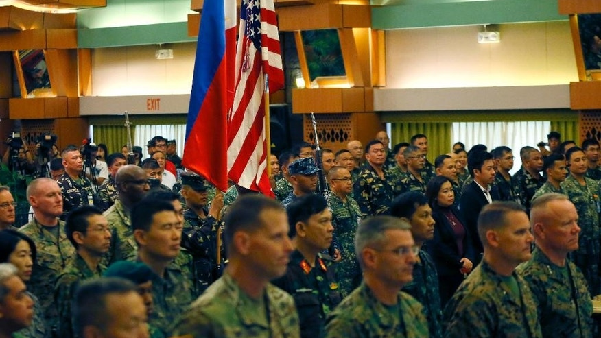 U.S. and Philippine military officers stand at attention during the entrance of the colors at the opening ceremony of the annual joint U.S.-Philippines military exercise dubbed Balikatan 2016 (Shoulder-to-Shoulder) Monday, April 4, 2016 at Camp Aguinaldo, in suburban Quezon city, northeast of Manila, Philippines. The annual military drill, involving 5,000 U.S. personnel and 3,500 counterpart from the Philippines, is being conducted amidst tension in the South China Sea.(AP Photo/Bullit Marquez)