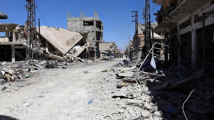 Ruins are seen at al-Qaryatain city in the central city of Homs, Syria on Monday, April 4, 2016. Syrian troops and allied militiamen pressed on with an offensive against Islamic State militants in central Syria on Monday, clashing with the extremists around the town of Qaryatain a day after it was captured by pro-government forces.  The Obama administration says Iran is drawing down its elite fighting force from Syria, yet Iran is still taking casualties and Tehran said Monday it has dispatched commandos to the war despite a partial cease-fire that took effect a month ago.  (AP Photo)