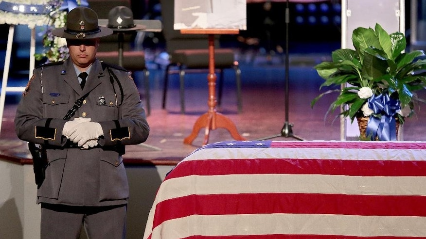A Georgia state trooper stands watch as an honor guard over the casket of Virginia trooper Chad Dermyer before his funeral Tuesday, April 5, 2016,  at Liberty Baptist Church in Hampton, Va. Authorities say Dermyer was fatally shot by James Brown III at the busy bus terminal, where police were holding a counterterrorism training exercise. (Rob Ostermaier/The Daily Press via AP, Pool)